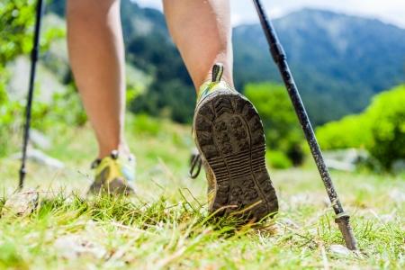 Mujer senderismo en las montañas, aventura y hacer ejercicio. Nordic Walking en el soleado verano al aire libre naturaleza. Piernas y zapatos deportivos caminar sobre la hierba