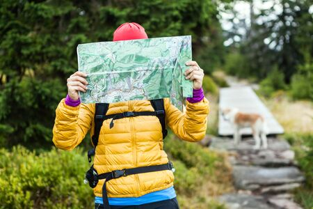 Woman hiking and reading map in forest, hiker with dog lost in autumn wilderness, Karkonosze Mountains in Poland photo