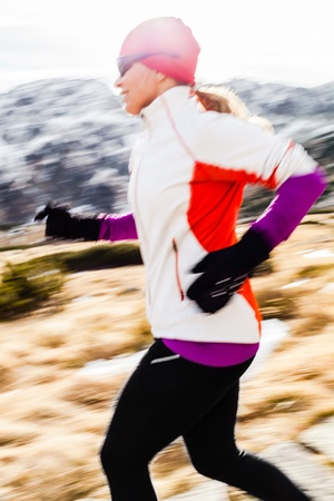 Young woman running in mountains on winter fall sunny day  Female runner exercising outdoors in nature, sunset  photo
