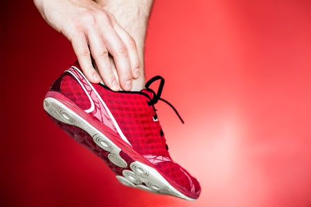 physical: Physical running injury and leg ankle pain, sport shoes and hand massage over red background