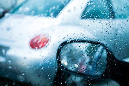 stoplights: Car windshield and mirror with rain drops during storm and blurred stoplights Shallow depth of field with focus on the mirror  Stock Photo