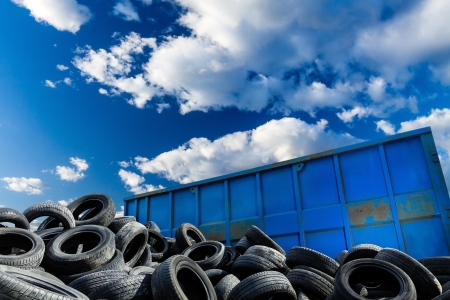 summer tire: Recycling business with metal container and car tires over blue sky  Ecology and recycle industry, saving nature and environment  Stock Photo