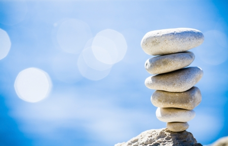 stability: Stones balance, hierarchy stack over blue sea in Croatia  Spa or well-being, freedom and stability concept on rocks  Stock Photo