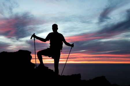 Male silhouette hiker with walking sticks on top of mountain looking at beautiful night landscape  photo
