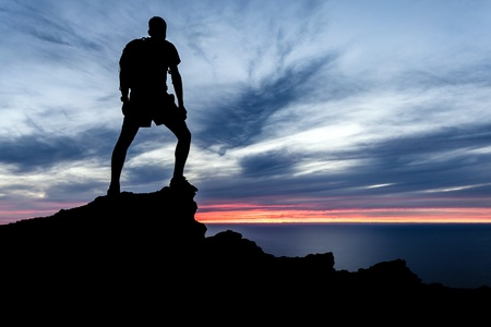 Male silhouette hiker with backpack on top of mountain looking at beautiful night landscape