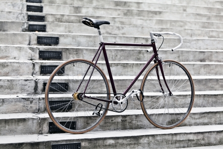 road bike: City bicycle fixed gear and concrete stairs  Vintage retro road bike over gray urban background