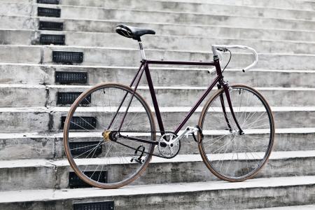 fixed: Ciudad de la bicicleta de artes fijos y escaleras de hormig�n Vintage bicicleta retro vial sobre fondo gris urbana