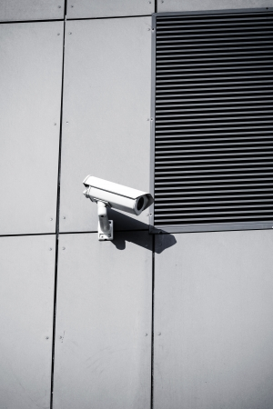 White security camera on office building, safety system  CCTV cam looking around and protecting a business
