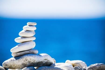 Stenen balans, hiërarchie stack over blauwe zee in Kroatië Spa of welzijn, vrijheid en stabiliteit concept op rotsen Stockfoto