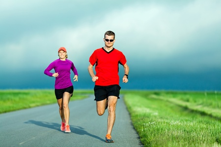 Man and woman runners running on country road in summer sunset photo
