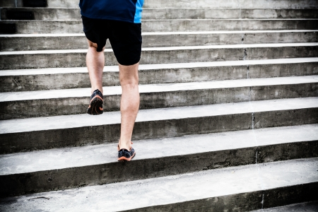 concrete stairs: Man runner running on stairs in city Stock Photo