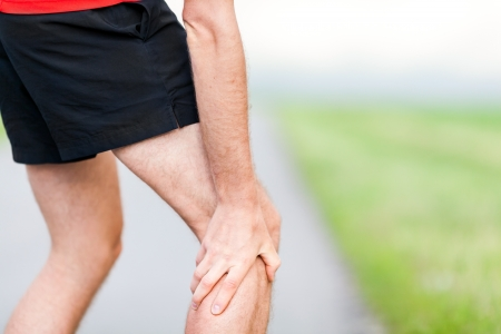 physical injury: Runner leg and muscle pain during running training outdoors in summer nature