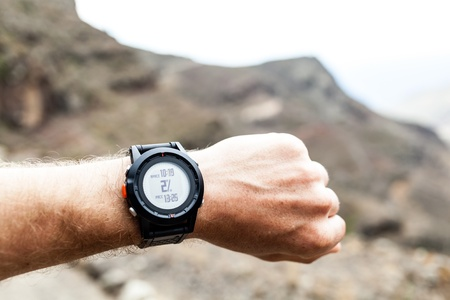 wristwatch: Runner on mountain trail looking at sportwatch