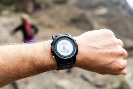 Runner on mountain trail looking at sportwatch, checking performance or heart pulse photo