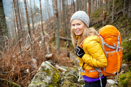 backpackers: Woman hiking in autumn forest in mountains