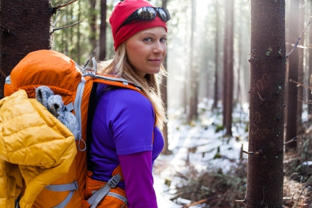 Woman hiking in white winter forest