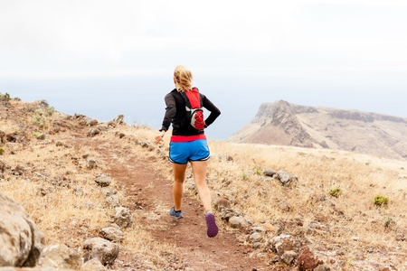 Young woman running on trail in mountains on summer day