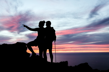 Man and woman hiking silhouette in mountains, sunset and ocean. Male and female couple hikers with walking sticks on top of mountain looking at beautiful night landscape.