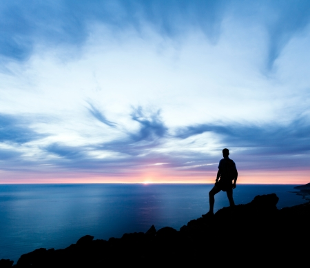 hiking trail: Man hiking silhouette in mountains, sunset and ocean. Male hiker with backpack on top of mountain looking at beautiful night landscape.