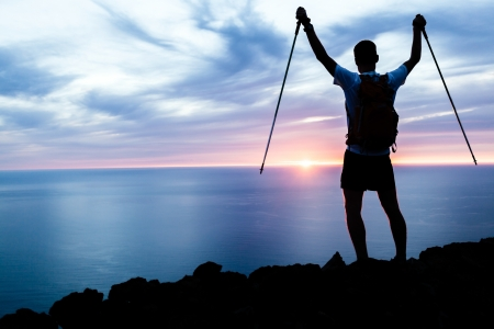 Man hiking silhouette in mountains, sunset and ocean. Male hiker with walking sticks on top of mountain looking at beautiful night landscape. Banco de Imagens