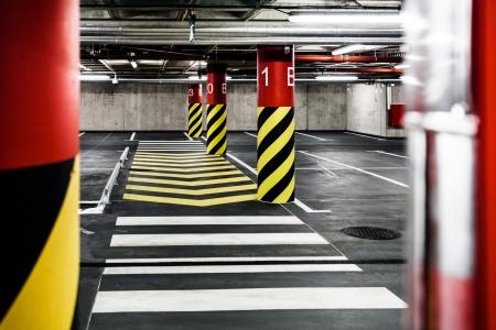 Parking garage underground interior, pedestrian crossing, neon lights in dark industrial building, modern public construction