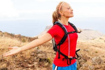 female jogger: Corredor de la mujer joven que disfruta de d�a de verano en las monta�as con los brazos extendidos. Mujeres corredor ejercicio al aire libre en la naturaleza, La Gomera Islas Canarias.