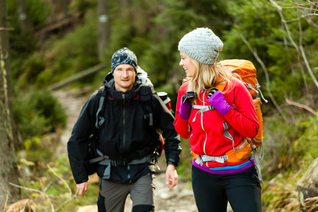 Man and woman hikers trekking in mountains. Young couple walking with backpacks in forest, Tatras in Poland.