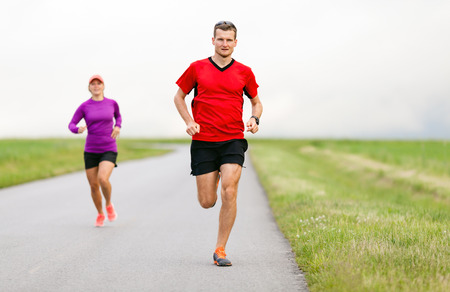 Man and woman runners running on country road in summer nature. Young people training and doing workout, sport and fitness outdoors. photo
