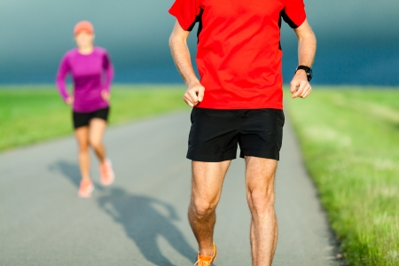 Man and woman runners running on country road in summer sunset. Young people training and doing workout for marathon, sport and fitness outdoors in nature. photo