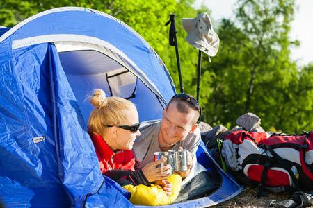 Man and woman hikers camping in summer nature. Happy young couple backpackers camping in tent, drinking coffee in morning sunny summer day. photo