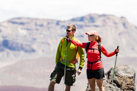 Man and woman hikers trekking in summer mountains. Young couple on rocky mountain range looking at beautiful view. Stock Photo