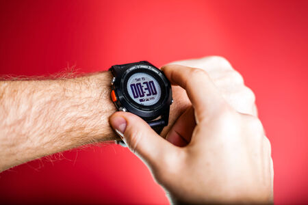 Male runner ready to run with sport watch. Taking puls or checking gps position wristwatch. Man and fitness, exercising concept on red background photo