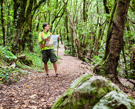 Man hiker hiking in green forest. Young male looking at map and planning trip or get lost in green forest, La Gomera, Canary Islands. photo