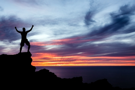 Man hiking silhouette in mountains, sunset and ocean. Male hiker with arms outstretched on top of mountain looking at beautiful night landscape. Banco de Imagens