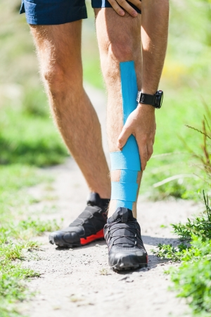 Man runner running on country road. Young athlete male holding leg with phisical injury, kinesiology taping, kinesiotape in sport use.