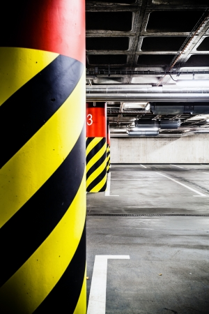 Parking garage underground inter  Concrete grunge industrial parking lot and column with warning sign, industrial inter  Stock Photo - 23294572