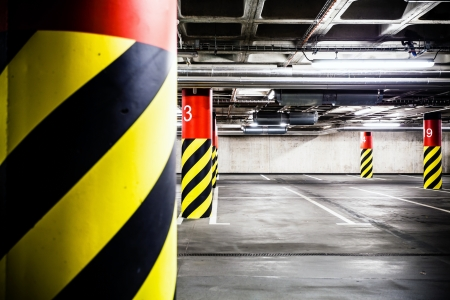 Parking garage underground interior  Concrete grunge wall and column with warning sign, industrial interior  Stock Photo - 23294570