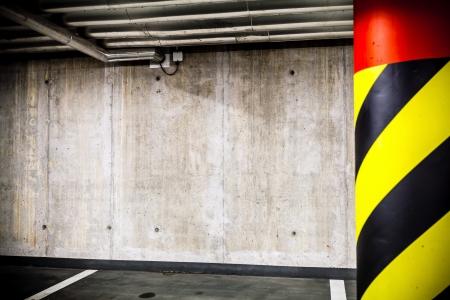parking lot interior: Parking garage underground interior  Concrete grunge wall and column with warning sign, industrial interior