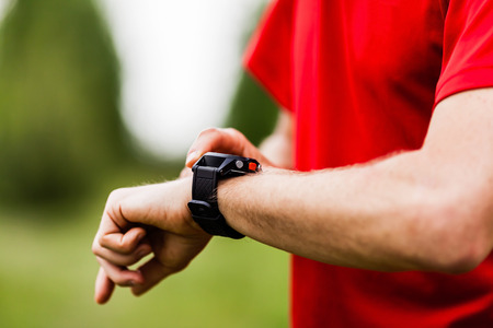 watch: Runner on mountain trail looking at sports watch, checking performance or heart rate pulse. Sport and fitness outdoors in nature. Stock Photo