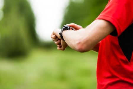 pulse: Runner on mountain trail looking at sportwatch, checking performance, heart rate pulse or GPS position. Sport, exercising and fitness outdoors in nature.