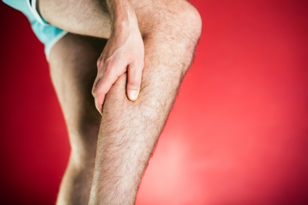 Running physical injury, leg calf pain. Runner sore body after exercising, red background photo