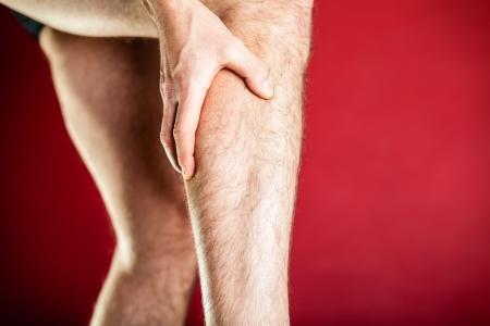 leg calf injury: Running physical injury, calf leg pain. Runner sore body after exercising, massage and medical examining, red background