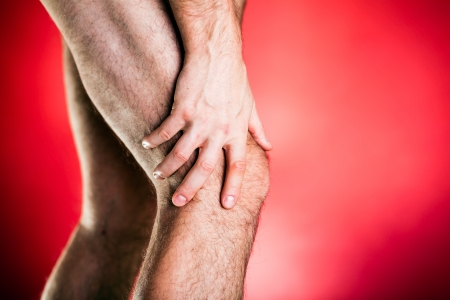 on hands and knees: Running physical injury, leg knee pain. Runner sore body after exercising, medical examining and massage, red background