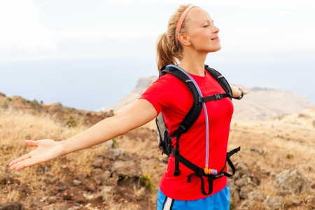 outstretched arms: Young woman runner enjoying summer day in mountains with arms outstretched. Female jogger exercising outdoors in nature, La Gomera Canary Islands. Stock Photo
