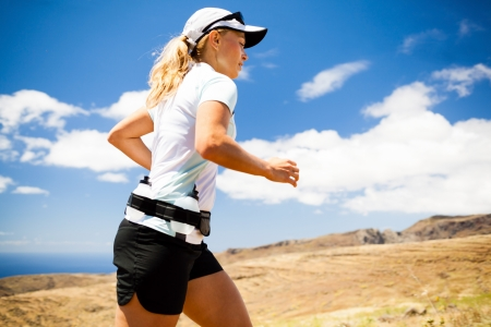 Young woman running in mountains on sunny summer day. Female runner exercising outdoors in nature, sunset. photo