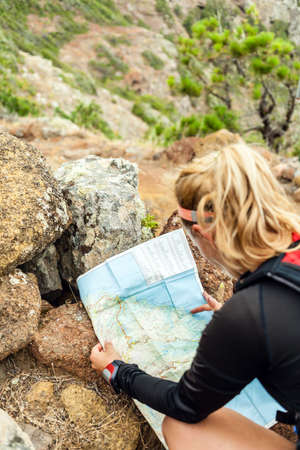 Young woman running on trail in mountains on summer day, checking map and direction. Female runner working out outdoors in nature on La Gomera, Canary Islands. photo