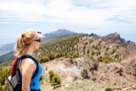 Hiking woman in mountains. Female hiker looking at beautiful view. Fitness and healthy lifestyle outdoors in summer nature, Canary Islands photo