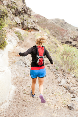 Young woman running on trail in mountains on summer day. Female runner exercising outdoors in nature on La Gomera, Canary Islands. photo