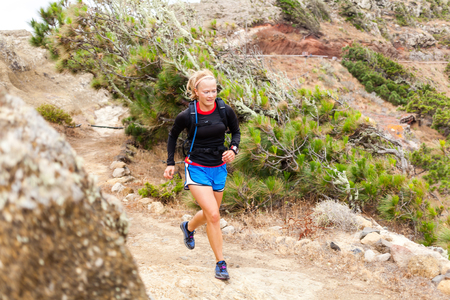 trail running: Young woman running on trail in mountains on summer day. Female runner exercising outdoors in nature on La Gomera, Canary Islands.