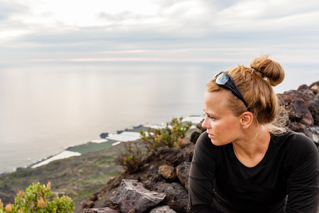Young woman looking at beautiful sunset in mountains, La Palma Canary Islands photo